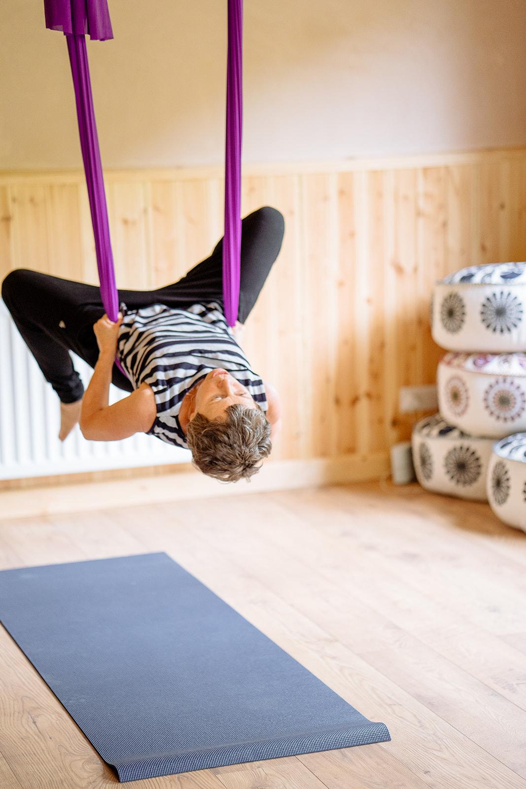 Lorraine doing an aerial yoga pose.