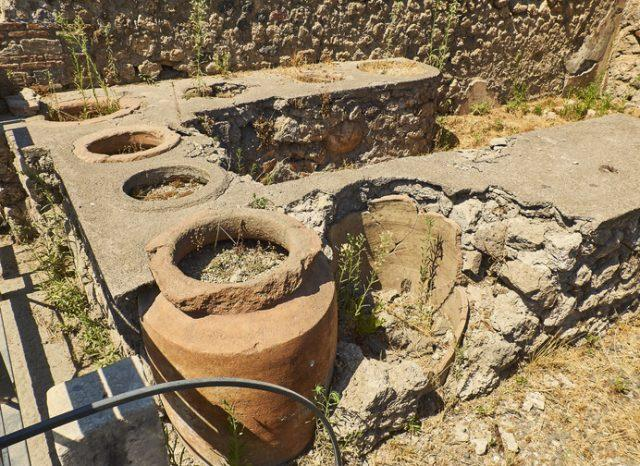 Thermopolium, dolias (jars) detail, of archaeological remains of the street Via Stabiana at Ruins of Pompeii. The city was an ancient Roman city destroyed by the volcano Vesuvius. Pompeii, Campania, Italy.