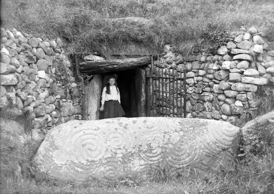 A young girl stands in front of the entrance to Newgrange in about 1905