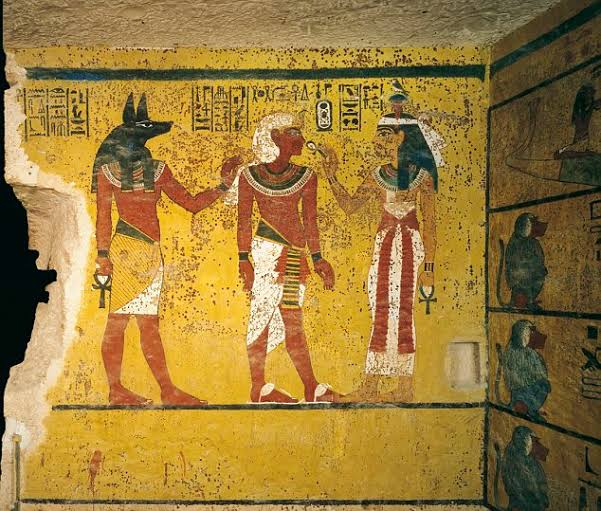 A fresco on the wall of his tomb shows Tutankhamun with the god Osiris