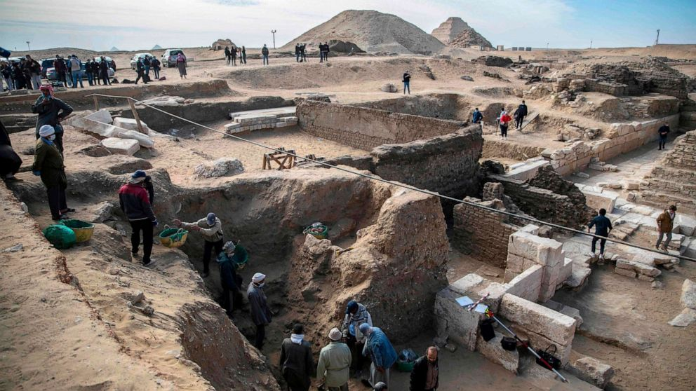 Workers excavate a site during the official announcement of the discovery by an Egyptian archaeological mission of a new trove of treasures at Egypt's Saqqara necropolis south of Cairo, Egypt, Jan. 17, 2021.