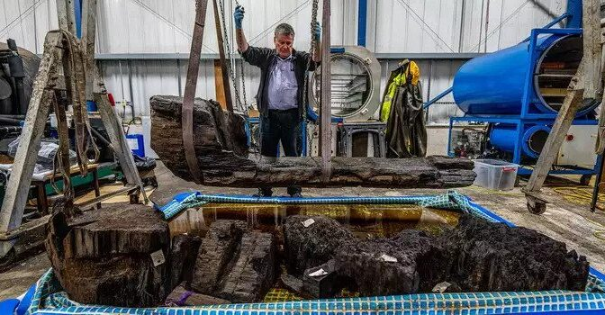 A coffin that was found in a golf course pond contains a 4,000-year-old man buried with an axe