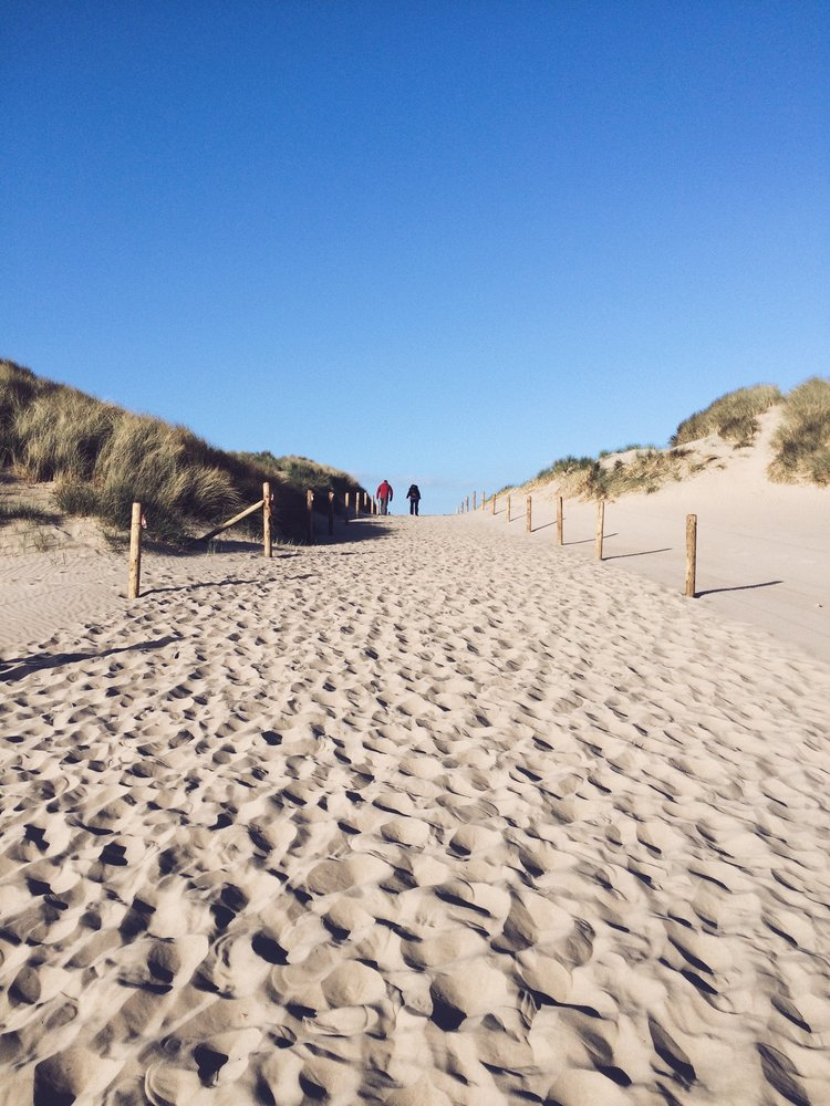 a couple leaving Harlech beach