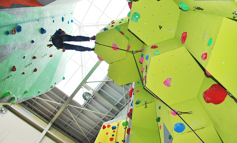 a person climbs up the Rock climbing wall in Harlech