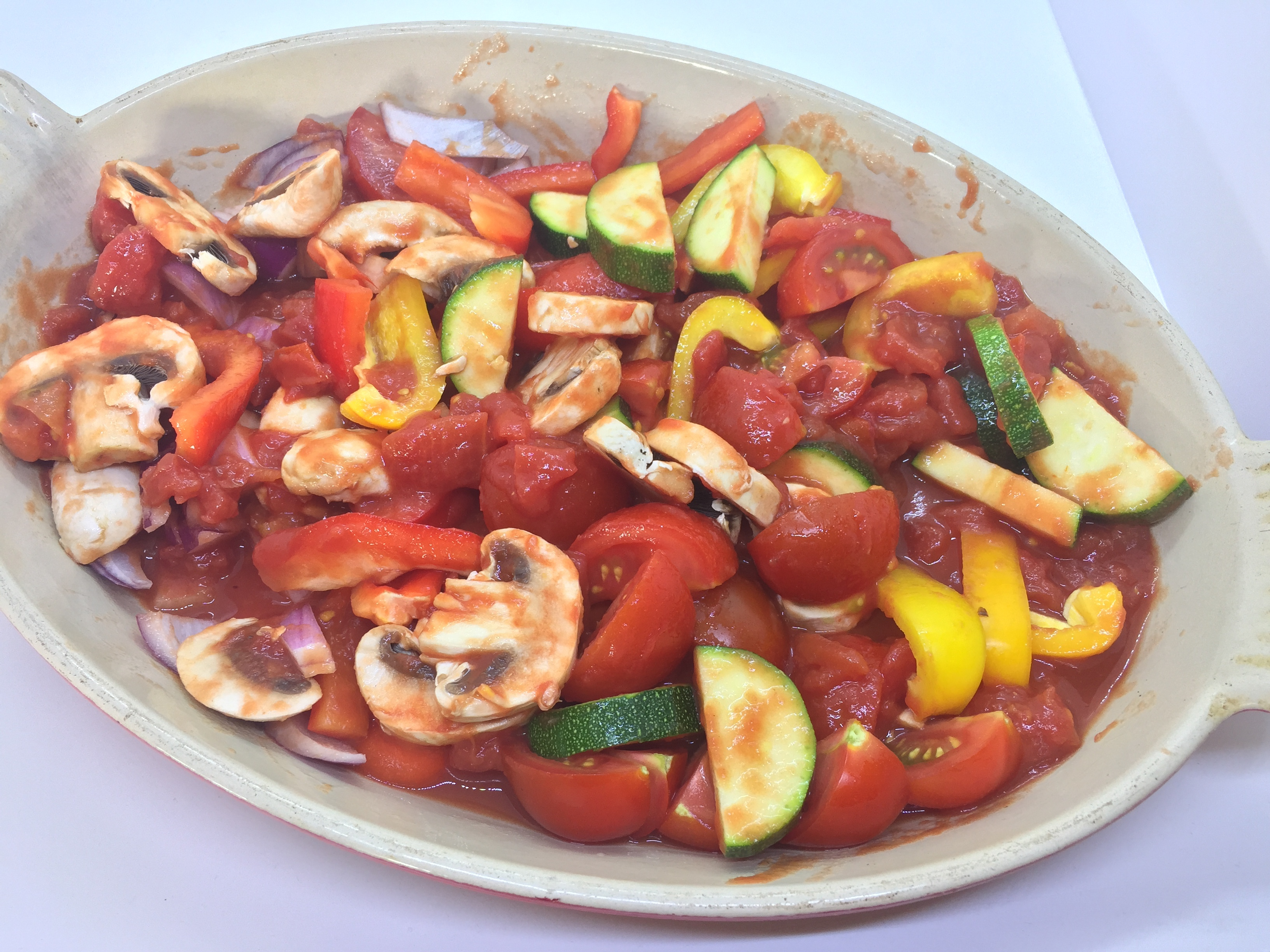 Adding tinned tomatoes and water