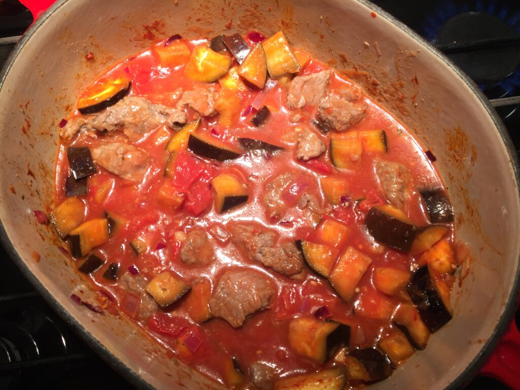 Adding the tomatoes, water and beef