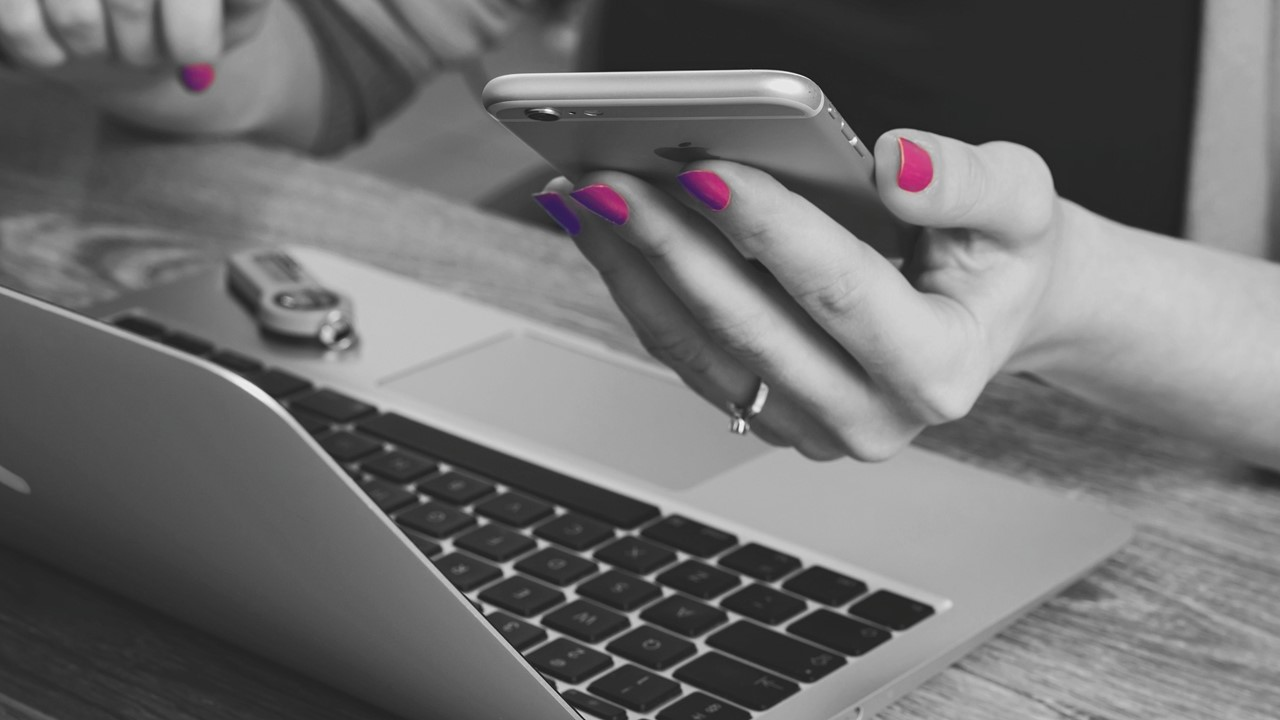 Women's hand holds iPhone and mac book wearing pink nail polish working from home