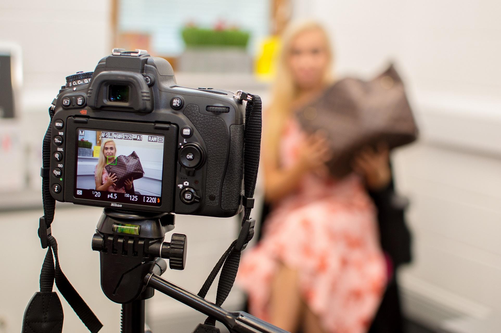 fashion blogger girl vlogging to camera with luxury louis vuitton handbag