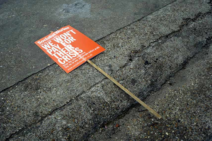 A discarded placard saying we won't pay for their crisis