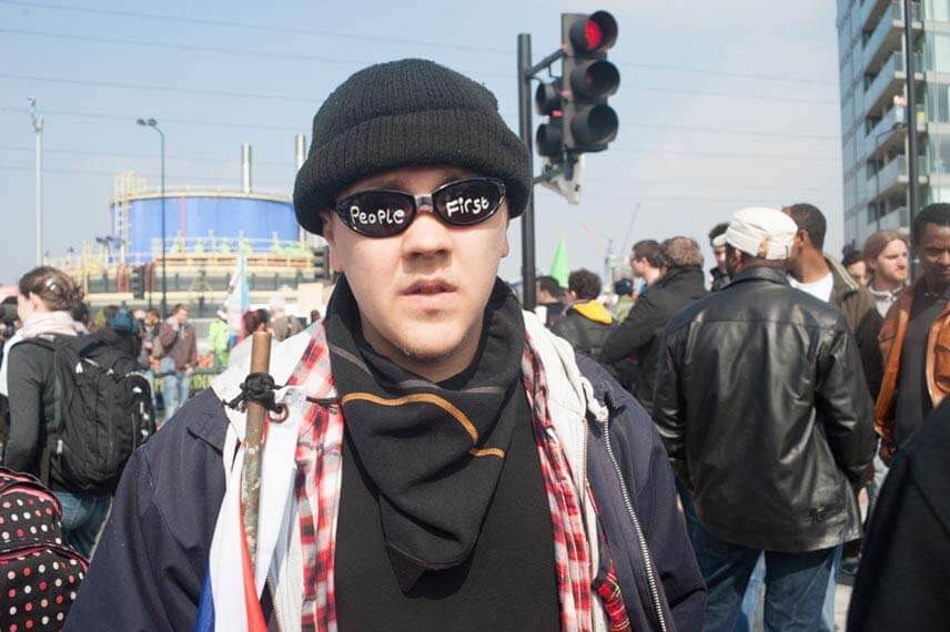 A protester with people first written on his sunglasses