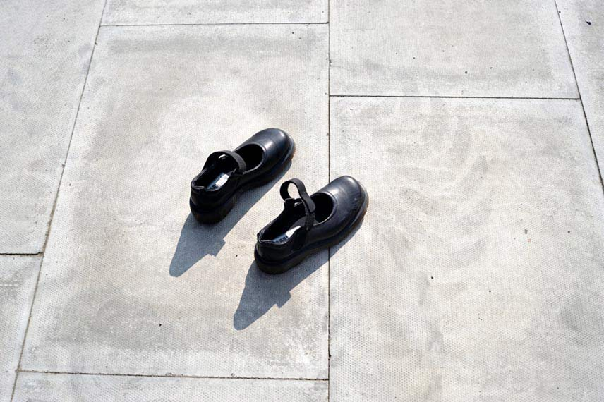 A pair of unused shoes surrounded by tyre marks