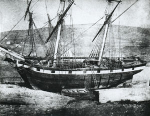 A wooden Brig docked in an unidentified Port