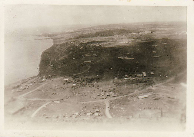 Old, faded black and white photo of Iwo Jima's coastline, sea just off to the left, land to the right