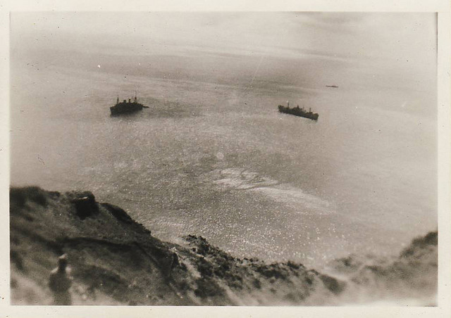 Black and white image taken from Mt Suribachi on Iwo Jima after the end of World War II, with two ships in the sea and rocky mountain in the foreground