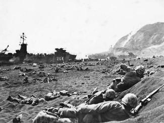 Marines burrow in the volcanic sand on the beach of Iwo Jima