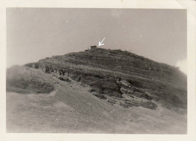 Black and white image of Mt Suribachi, with a radar shack on top indicated by a white arrow