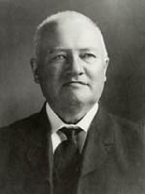 Black and white photo of J. E. Estienne, in white shirt and black suit and tie