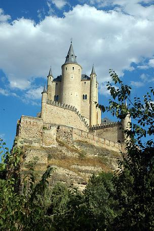 The Alcázar de Segovia in the Iberian Peninsula, against the background of a blue sky with cloud, trees in the foreground.