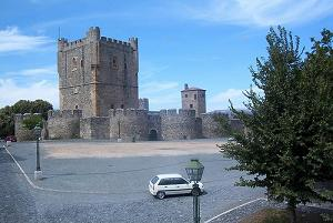 Picture of Bragança Castle, Portugal, with blue sky in the background, and a small white car in the foreground