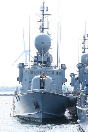 A grey fast attack craft of the the German navy, moored next to others,  with German flag at the prow