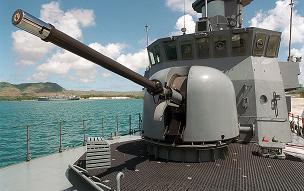 OTO Melara 76mm Super Rapid gun aboard a ship, blue sea and coast in the background