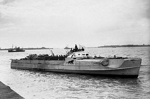 Black and white image of a German Schnellboote just off land, waving a white flag and with its crew up on deck