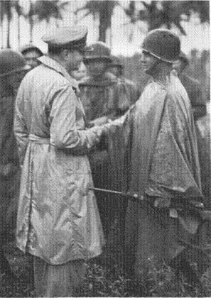 Black and white photograph of General Douglas MacArthur decorating the first man ashore on the Admiralty Islands, 2nd Lieutenant Marvin J. Henshaw, who is wearing a helmet and holding his rifle.