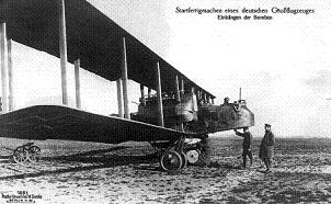 Black and white photo of a German Gotha bomber plane on the ground, being inspected by two military men