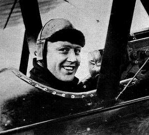 Black and white photo of Lieutenant Colonel Raymond Collishaw as a young man, sitting in the cockpit of his fighter plane and smiling
