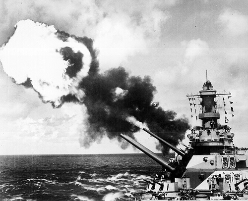 Black and white photo of battleship guns firing, with thick discharge of flame and smoke