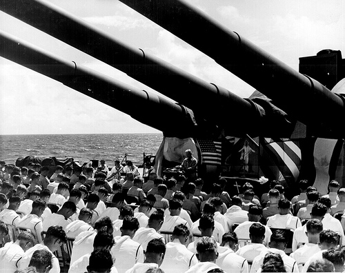 The crew of the USS SOUTH DAKOTA sit with bowed heads, while Chaplain N. D. Lindner reads the benediction held in honor of fellow shipmates killed in air action off Guam