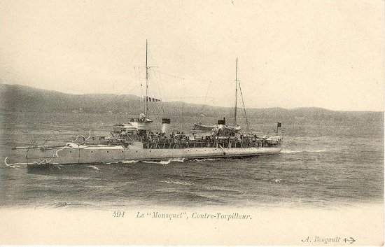 Black and white image (turned pinkish) of the small French destroyer warship, Mousquet, on the sea with land in the background