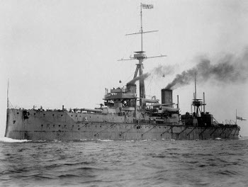 Black and white photo of HMS Dreadnought, a British Navy battleship, on the sea, steam coming out of its funnels.
