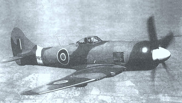 Grainy black and white photograph of a late production Tempest II in flight, with the pilot's face visible in the cockpit, and looking towards the camera