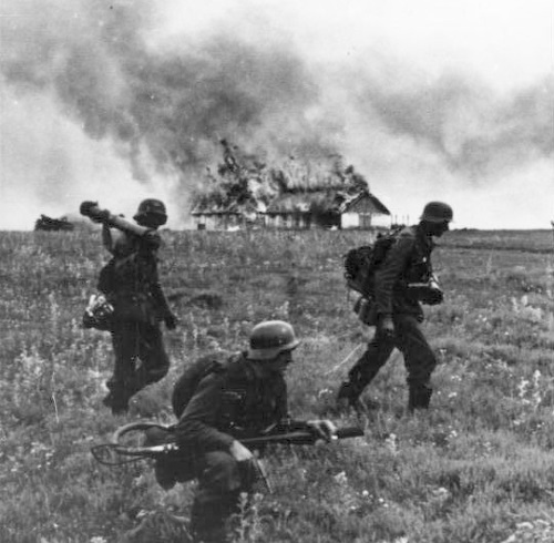German soldiers in front of a burning building