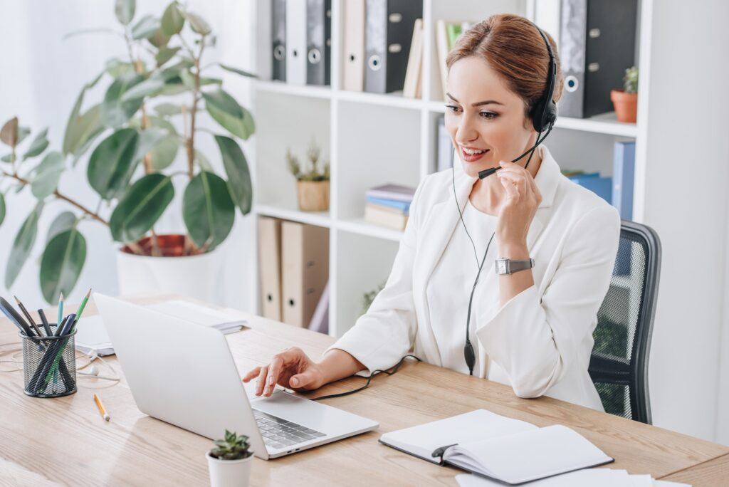 beautiful support operator working with headset and laptop in modern office