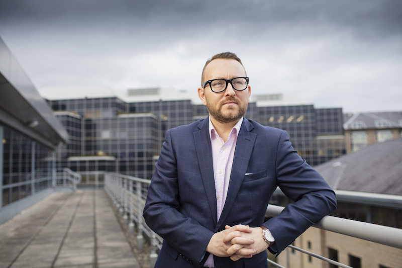 Corporate portrait of an executive standing on a rooftop terrace of an office building.