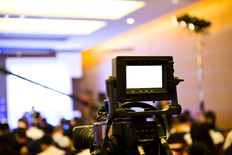 a video camera looking over the heads of an audience at a seminar
