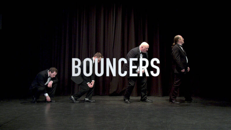 Marketing video still image showing members of a theatre production on stage.