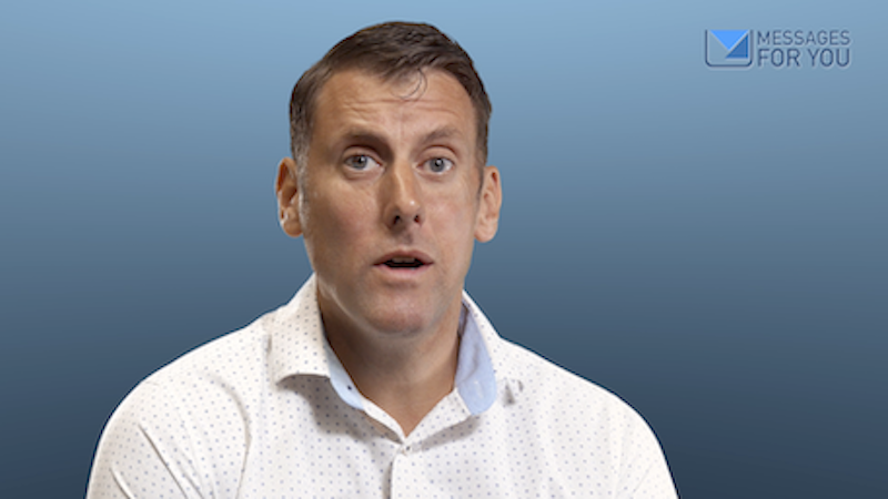 Talking head, corporate style video still image, showing a man talking to the camera.