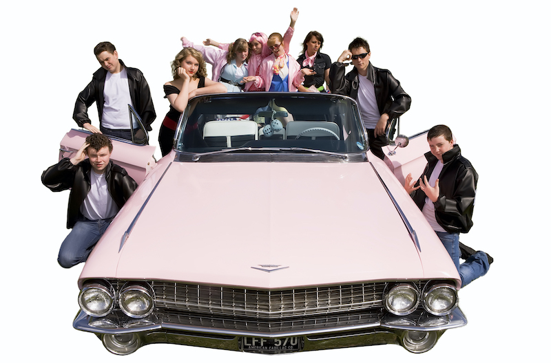 School event publicity photograph example: Student cast of  the musical Grease shown in and around a large pink Cadillac