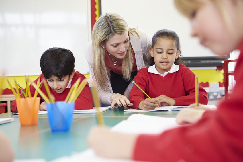 School marketing photography example of reportage style shot of a lesson in progress with a teacher helping a child.