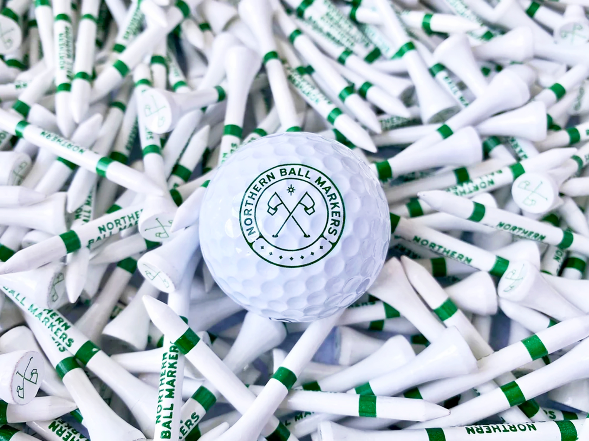 Northern Ball Markers branded golf ball design on top of golf tees
