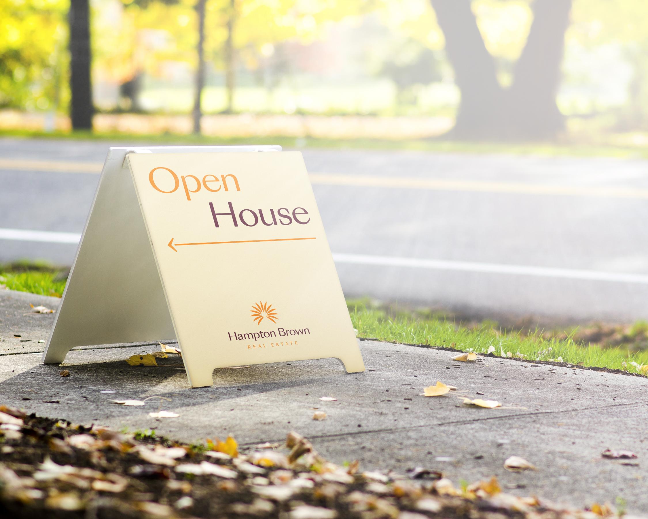 Hampton Brown open house a-board design on suburban pavement outside home