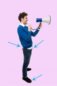 Side view portrait of a man shouting through megaphone