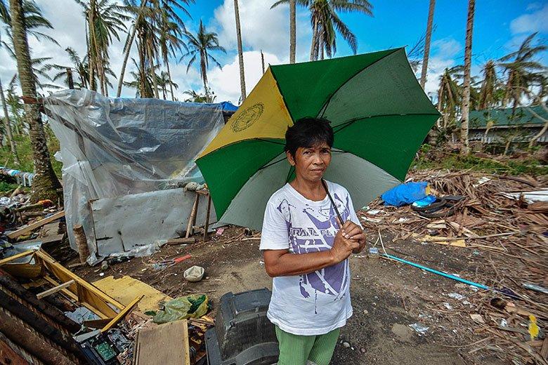 Photograph of flood-affected woman holding an umbrella