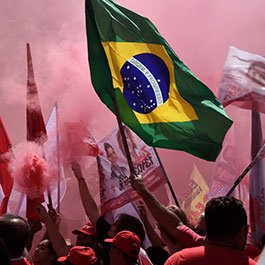 Photograph of Brazilian street protest with one protestor waving large Brazilian flag surrounded by people holding red smoke flares