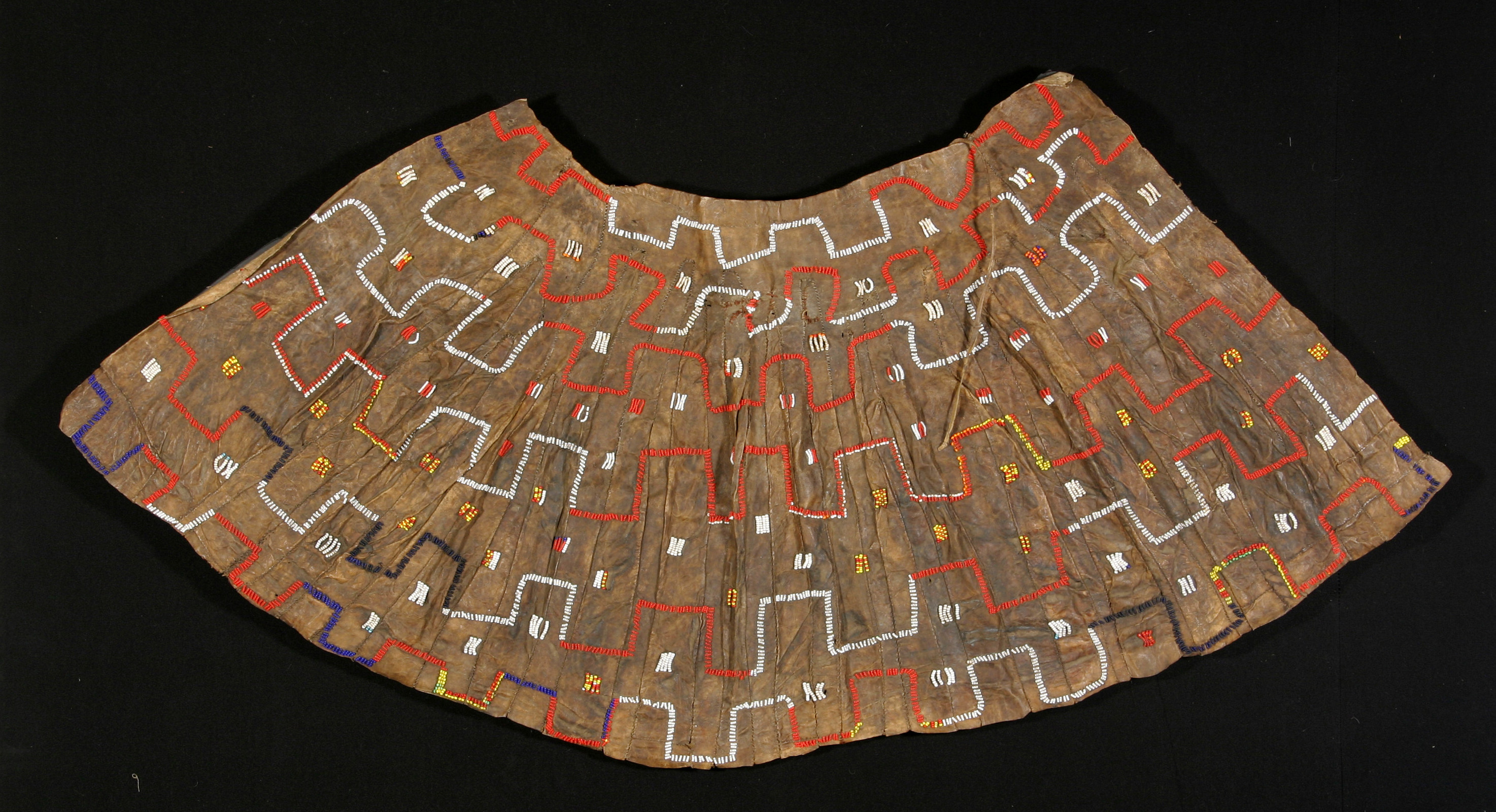"Iraqwa skirt, north Tanzania, early 20th century. Glass beads on leather; 31"" x60"". These types of skirts were made by Iraqwa girls as part of their 'marmo' (seclusion) initiation ritual. This ritual was abolished by the colonial appointed chief in the 1930's."