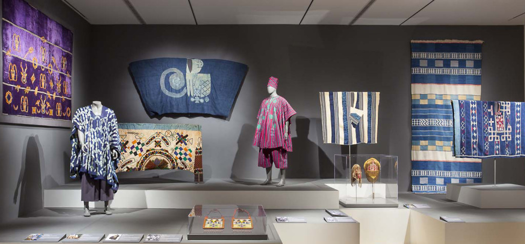 Gallery installation of 'Majestic African Textiles' at Indianapolis Museum of Art showing various West African narrow stripe woven cloths to the right, a Hausa agbaba robe on the wall left and a N'dop Cameroonian costume front left