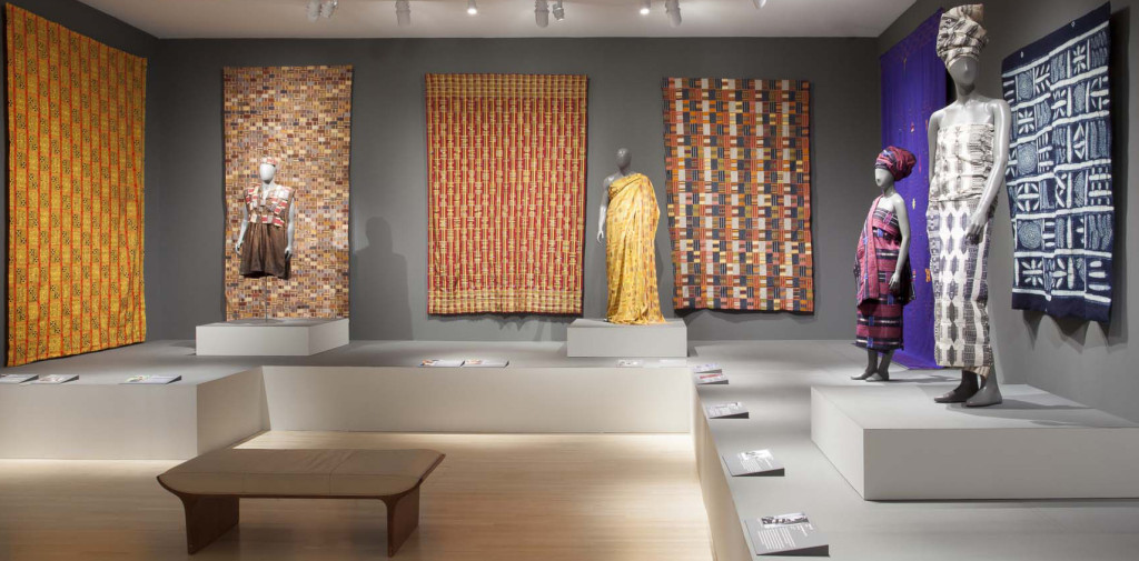 Gallery installation of 'Majestic African Textiles' at Indianapolis Museum of Art showing various Ewe and Kente narrow strip woven cloths, alongside Cameroonian and Nigerian cloths